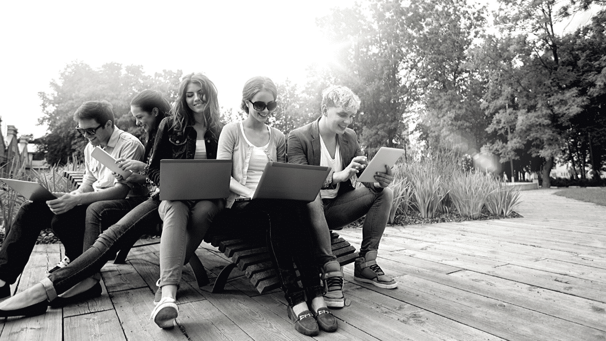 group of students gathered outside on the University Campus of Bordeaux to work on their laptops