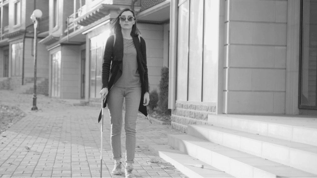 Une femme déficiente visuelle marche dans la rue à l'aide d'une canne