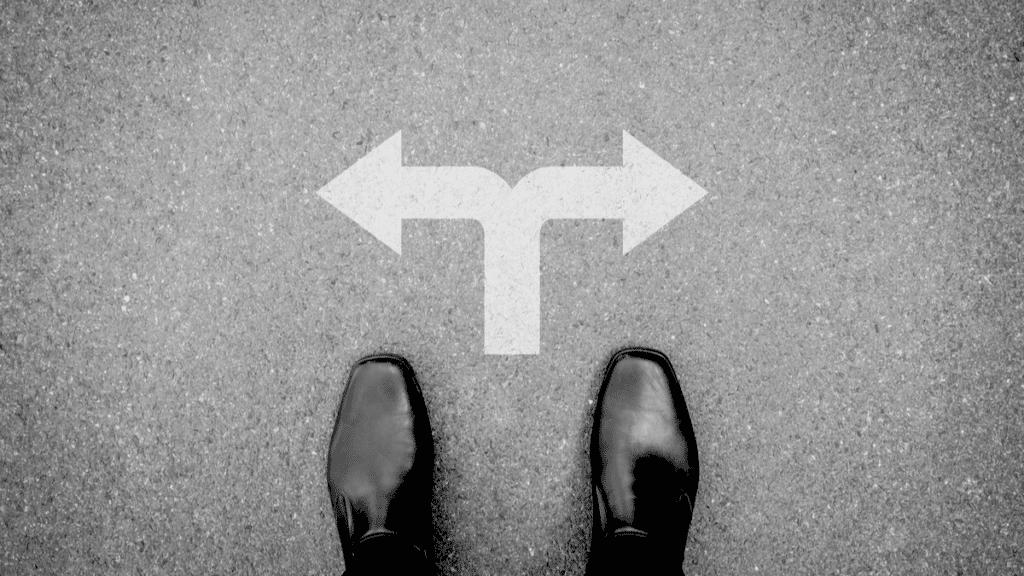 Un homme d'affaires aux chaussures noires doit prendre une décision entre les deux directions indiquées par la flèche au sol