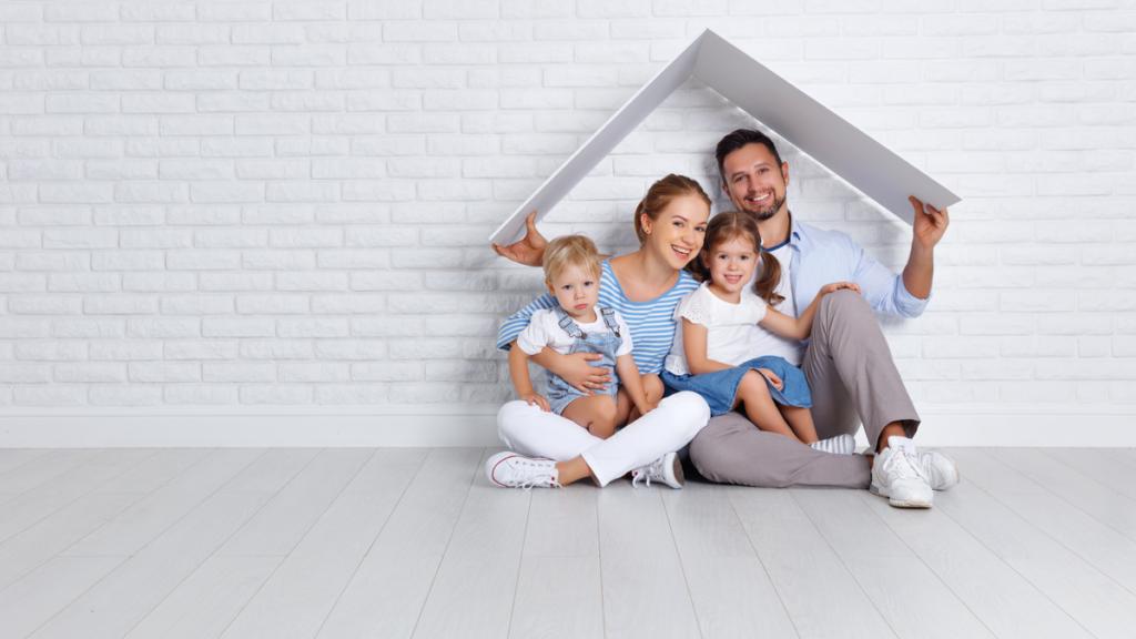 Une jeune famille souriante au milieu de leur nouveau logement.