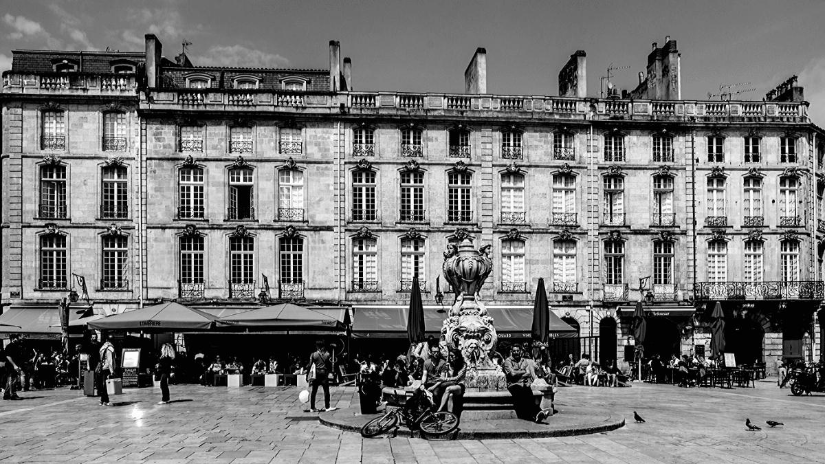 façades de bâtiments bordelais typiques abritant des appartement anciens parfaits pour des investissements dans l'immobilier locatif au dessus des cafés, bars et restaurant sur une place pavées ornée d'une fontaine à Bordeaux