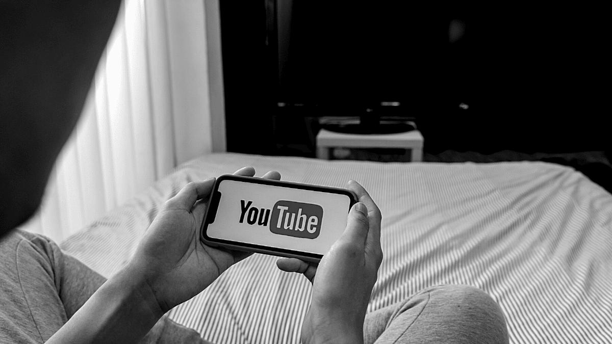 jeune homme regardant une vidéo Youtube sur son smartphone