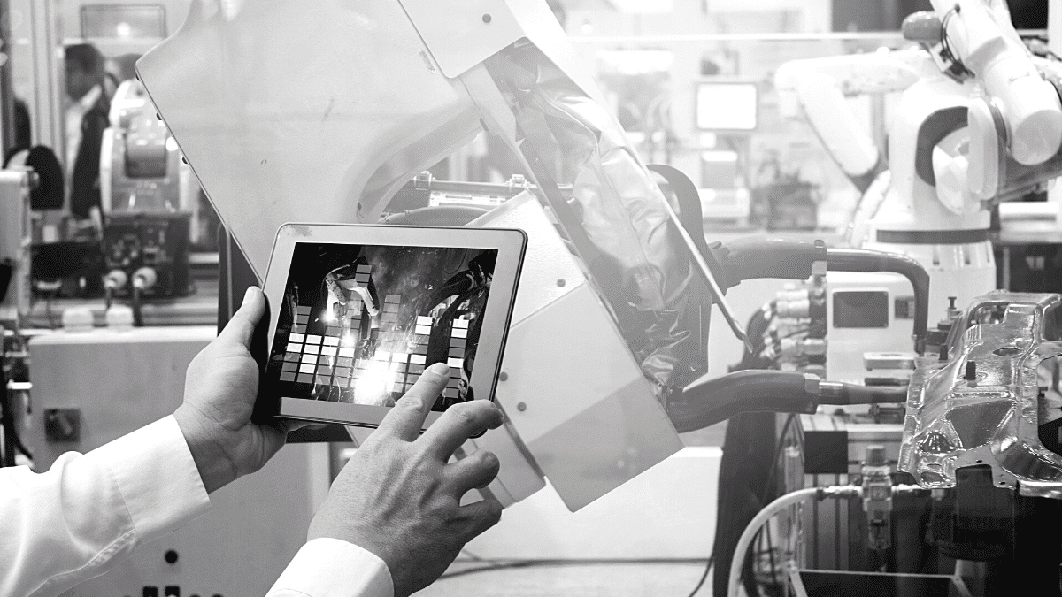 A himme monitors on his tablet, digital the programming of an automobile production line