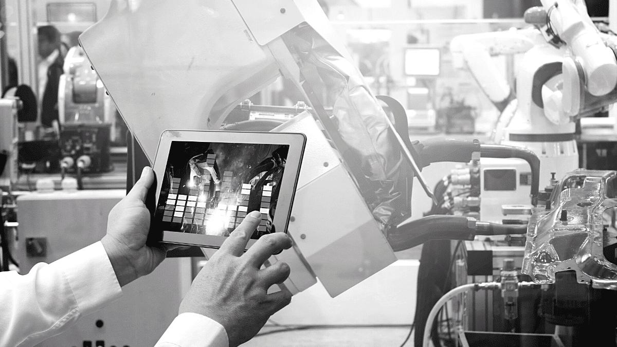 Un homme surveille sur sa tablette ,numérique la programmation d'une chaîne de production automobile